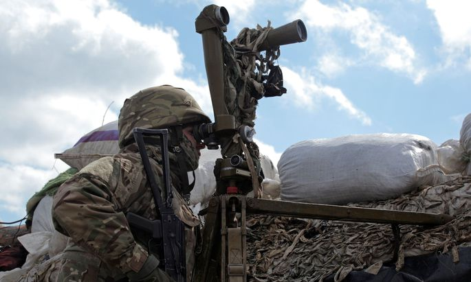 Ukrainischer Soldat beobachter den russischen Truppenaufmarsch an der Grenze