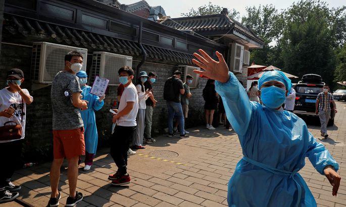 Vor dem abgesperrten Xinfadi-Markt in Peking gestikuliert eine aufgeregte Krankenschwester im Schutzanzug.