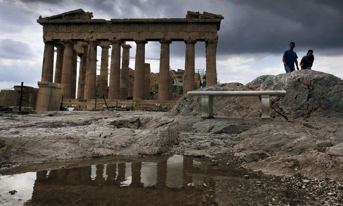 Tourists visit the Athens Acropolis during a rainy day