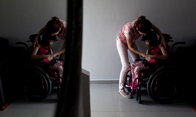 Benavides sits her daughter Graciela, who suffers from Lennox-Gastaut syndrome, a debilitating form of epilepsy, in a wheelchair at her house in Monterrey