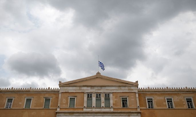 A Greek national flag flies at half mast over the parliament building as a period of national mourning is declared for the victims of wildfires, in Athens