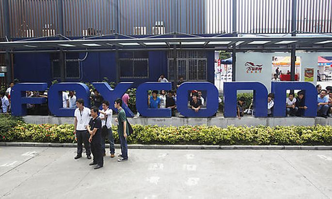 Company staff stand in front of the Foxconn logo at the entrance of the Foxconn complex in the southe