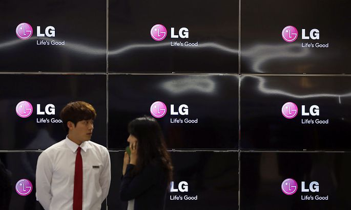 Visitors stand in front of LG Electronics´ TV sets during World IT show 2013 at the Coex convention centre in Seoul