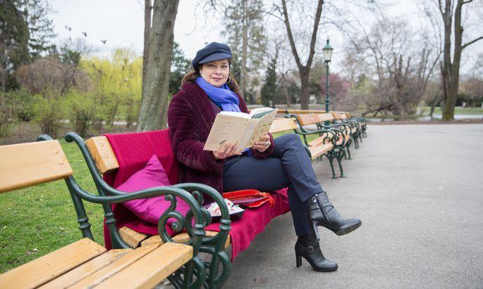 Ingrid Lassnig liest Parkbesuchern auf einer Bank im Stadtpark vor.