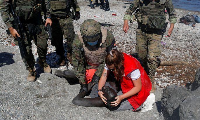 Eine Mitarbeiterin des spanischen Roten Kreuzes und Soldaten helfen einem erschöpften Migranten an der spanisch-marokkanischen Grenze.