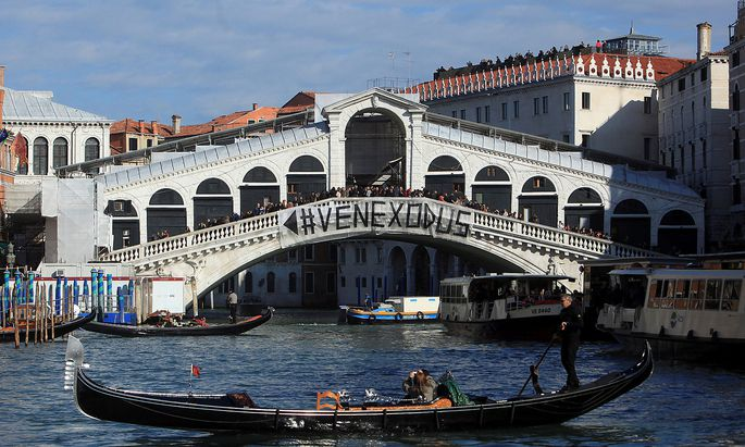 A banner reading ´Venice Exodus´ is displayed on the Rialto Bridge in a protest that calls for the authorities to think of the local community and not just about tourists, in Venice