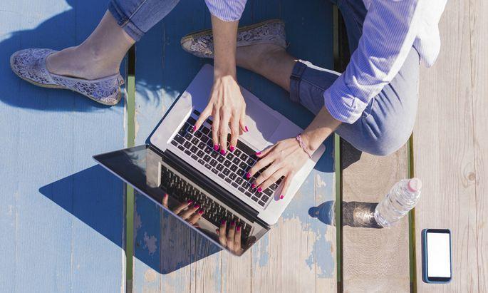 Woman using laptop on wooden boardwalk model released Symbolfoto PUBLICATIONxINxGERxSUIxAUTxHUNxONLY