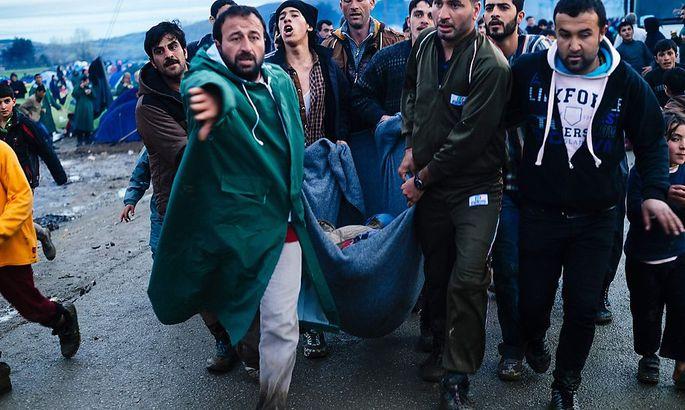 Flüchtlinge tragen eine verletzte Frau an der griechisch-mazedonischen Grenze.
