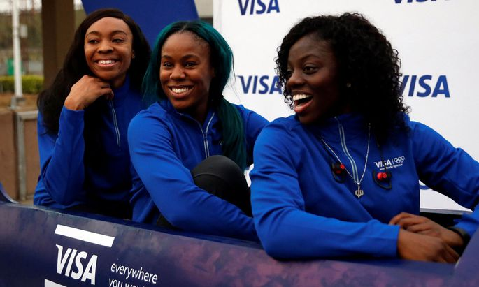 Nigerian Women's Bobsled Team Ngozi Onwumere, Akuoma Omeoga and Seun Adigun smile in a bobsled upon their arrival in Lagos