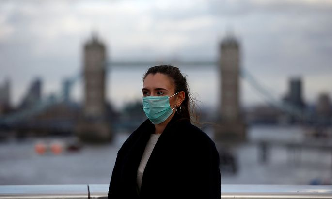 Woman wearing a protective face mask is seen on London Bridge in London