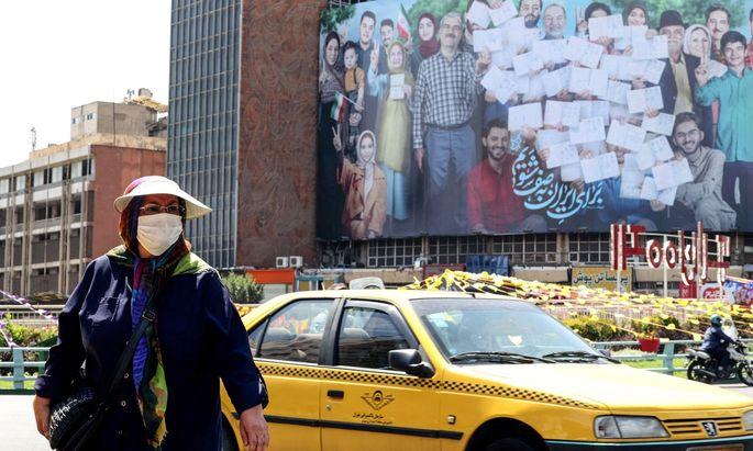 Straßenszene aus Teheran, im Hintergrund ist ein Wahlplakat zu sehen. Ebrahim Raisi, der erzkonservative Chef der Justiz, stand schon vorher als Sieger fest.