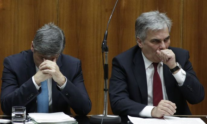 Austrian Finance Minister Spindelegger and Chancellor Faymann wait for the beginning of a session of the Parliament in Vienna