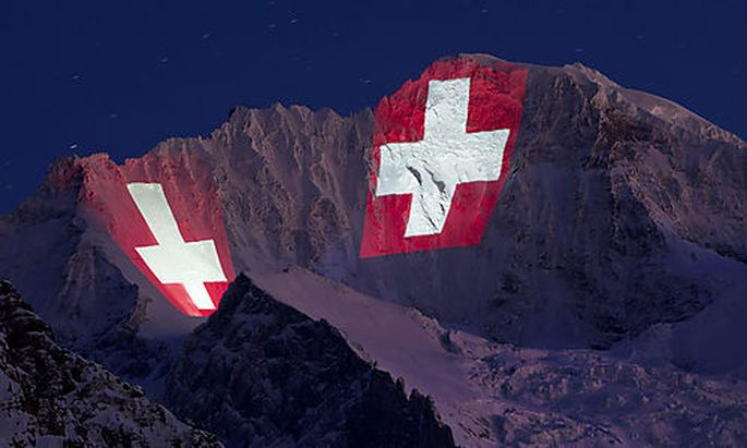 In this photo taken Wednesday, Jan. 11, 2012, the Jungfrau mountain in the Alps is illuminated by Swi