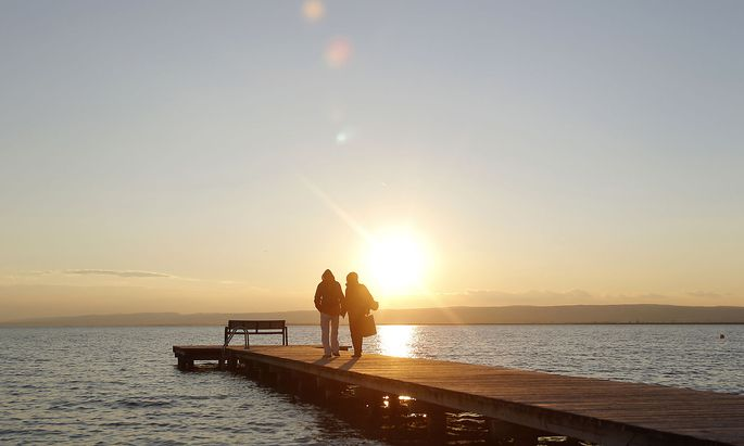 A couple walks on a dock at Lake Neusiedl (Neusiedlersee) in Weiden