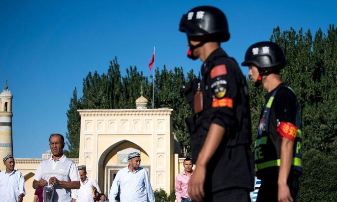 Chinesischer Überwachungsstaat. Polizisten auf Patrouille bei der Id-Kah-Moschee in der Stadt Kashgar.