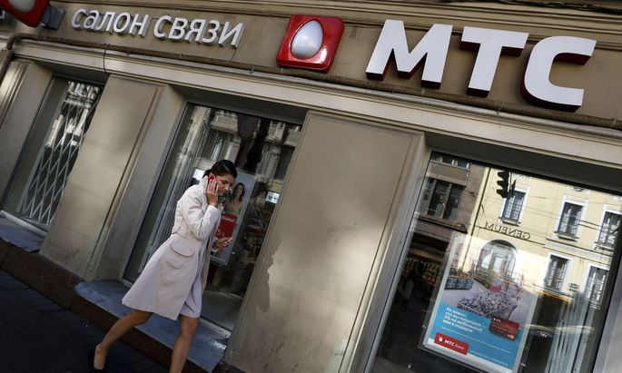 Woman passes by an office of mobile phone operator MTS, in which Sistema has an effective ownership stake, in St. Petersburg