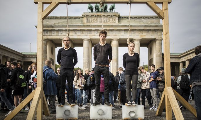 Aktion vor dem Brandenburger Tor in Berlin mit schmelzenden Eisblöcken. Währenddessen stellte die Regierung einen Aktionsplan fürs Klima vor.