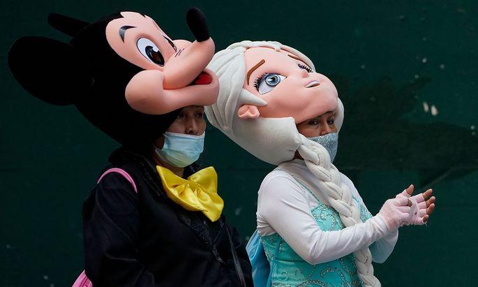 Masken-Parade auf dem New Yorker Times Square mit Mickey und Elsa. Die steigenden Fallzahl sorgen auch in den USA für Debatten.