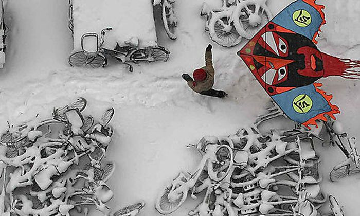 In this photo taken Monday, Jan. 4, 2010, a child flies a kite at a snow-covered bicycles parking pla