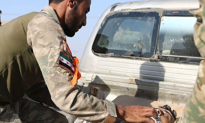 Ein Kurdenkämpfer kümmert sich um einen verletzten Kollegen.APA  AFP  NAZEER AL-KHATIB