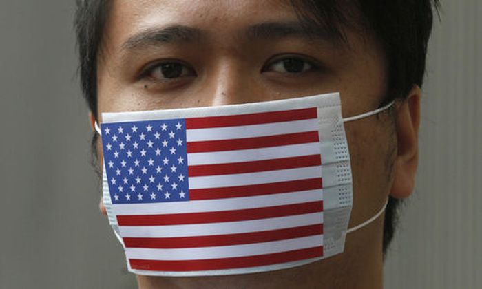 A supporter of WikiLeaks founder Julian Assange wears the mask featuring the American National flag d