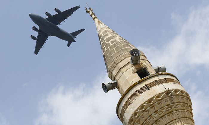 File photo of a U.S. Air Force Boeing C-17A Globemaster III large transport aircraft flies over a minaret after taking off from Incirlik air base in Adana