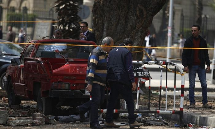 Police officers inspect near the site of a series of explosions in front of Cairo University