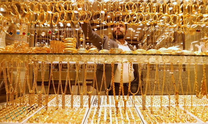 An Iraqi goldsmith arranges gold wristbands at his shop in Baghdad