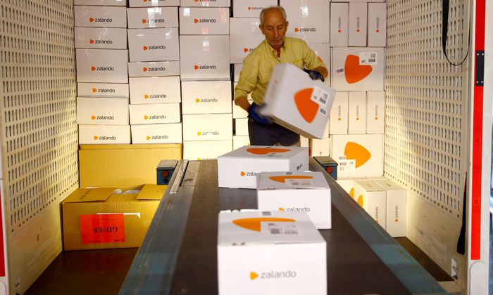An employee places parcels of online mail order company Zalando on a conveyor at the parcel distribution center of Swiss Post in Frauenfeld