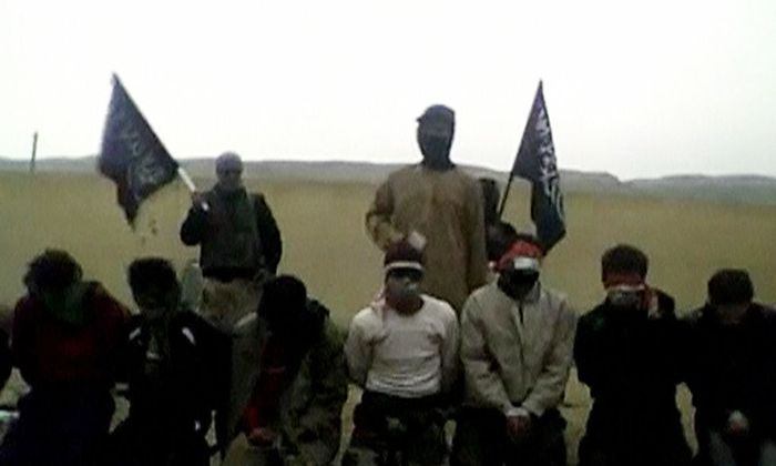 Still frame from video obtained from a social media website shows three rebels, two of them carrying Jabhat al-Nussra flags, stand behind a row of 11 kneeling men prior to executing them in what is said to be Deir al-Zor