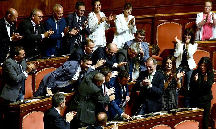 Matteo Salvini bekommt von seinen Parteikollegen nach seiner Rede im Parlament eine Menge Schulterklopfer.