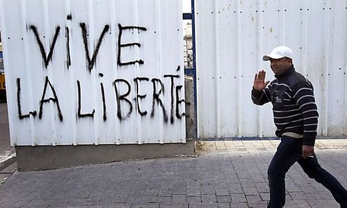 A man waves as he walks past graffiti reading long live liberty, Friday, Jan. 21. 2011in central T
