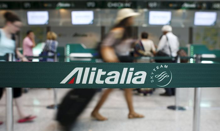 People walk in the Alitalia departure hall during a strike by Italy's national airline Alitalia workers at Fiumicino international airport in Rome