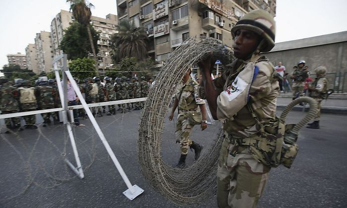A soldier carries barbed wire fencing near army soldiers taking positions in front of protesters who are against Egyptian President Mursi, near the Republican Guard headquarters in Cairo