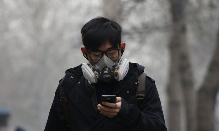 A man wearing a mask uses his mobile phone amid heavy smog after the city issued its first ever ´red alert´ for air pollution, in Beijing, China