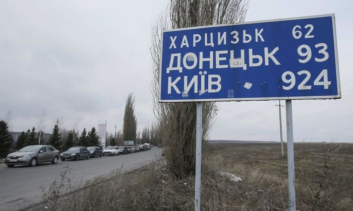 Cars queue to reach a border crossing point, before driving into Russian territory, outside the village of Uspenka