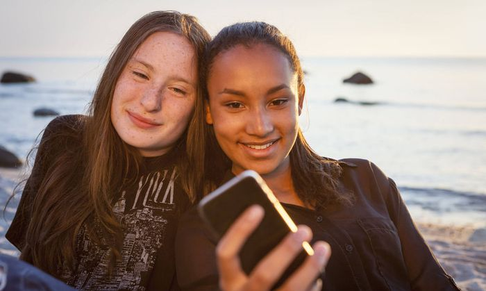 Germany Ruegen Two young female friends with smartphone at the beach model released Symbolfoto PUB