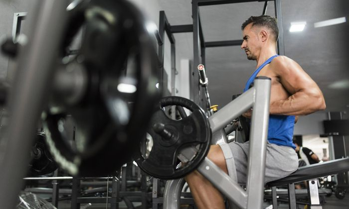 Man training with back exercise machine in gym model released Symbolfoto property released PUBLICATI