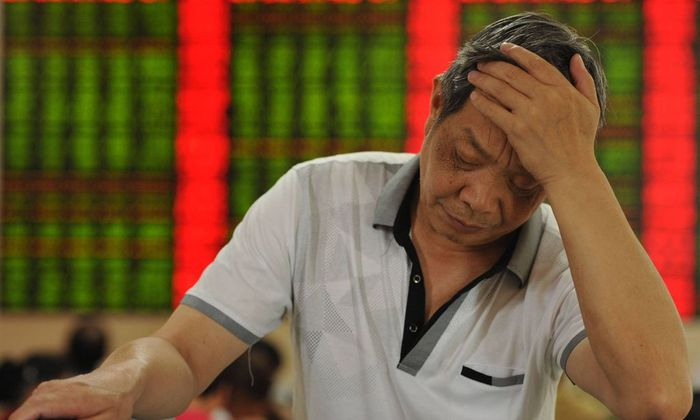 FUYANG CHINA JULY 02 CHINA OUT An investor reacts in front of an electronic board at a stock e