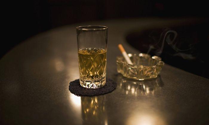 Glass of whiskey next to a cigarette in an ashtray PUBLICATIONxINxGERxSUIxAUTxONLY Copyright Aaronx