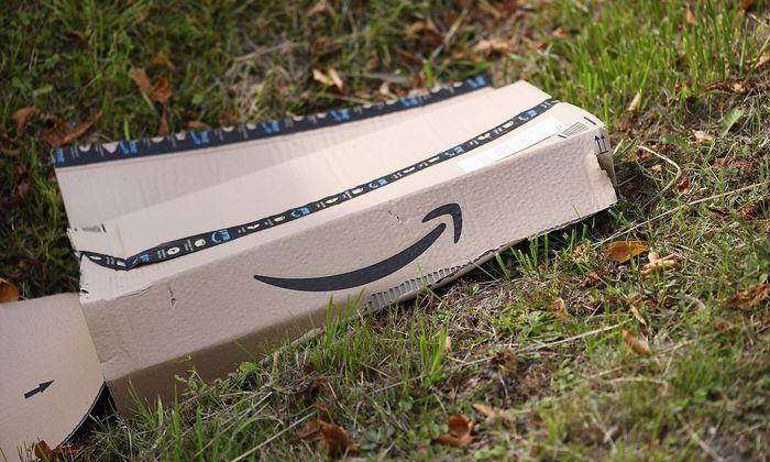 Versandkarton von Onlinehaendler amazon liegt im Straszengraben *** Shipping carton from online retai