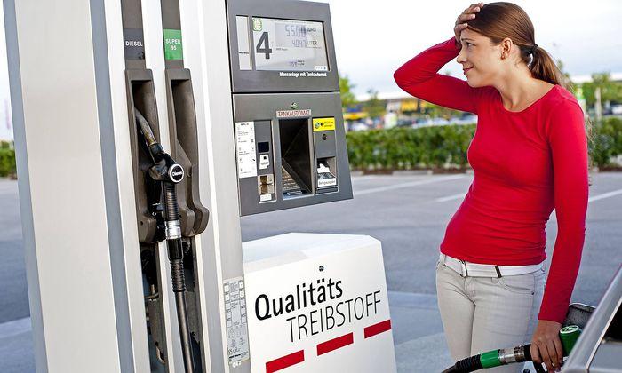 junge Frau steht an der Zapfsaeule einer Tankstelle und haelt sich mit Blick auf den Spritpreis fass