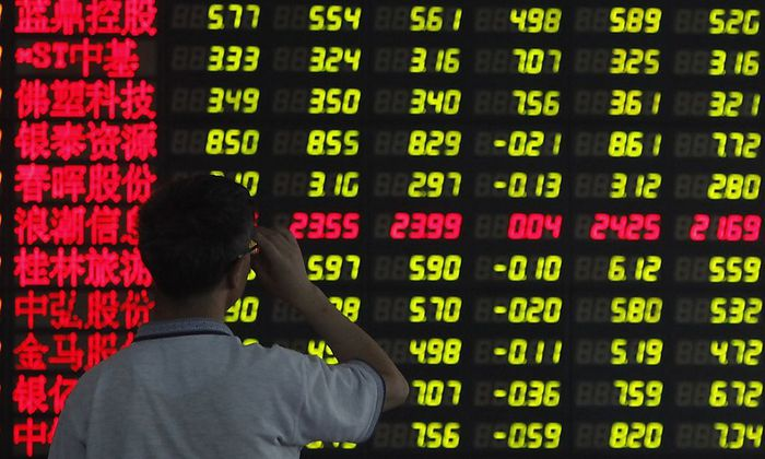 An investor reads information displayed on an electronic screen at a brokerage house in Shanghai