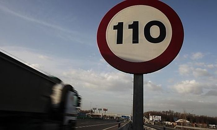 A truck drives past a speed limit sign on a highway outside Madrid