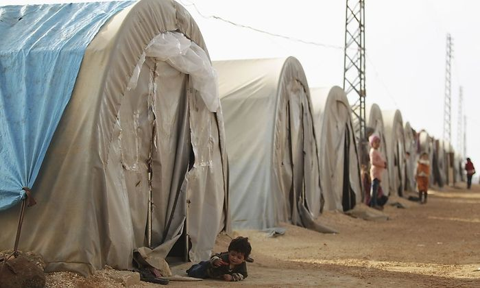 Children, who are internally displaced due to fighting between rebels and forces loyal to Syrian President Bashar al-Assad, wait outside tents at the Jarjanaz refugee camp in the southern countryside of Idlib