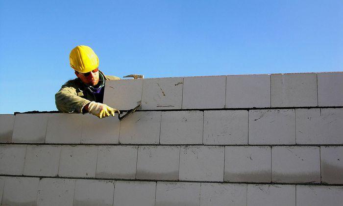 Bauarbeiter errichtet eine Ziegelmauer