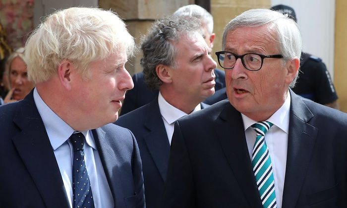 British Prime Minister Boris Johnson and European Commission President Jean-Claude Juncker talk as they leave after their meeting in Luxembourg