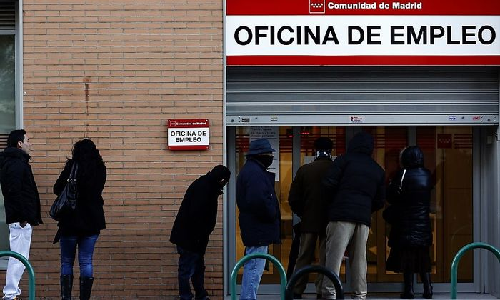People wait in line to enter a government-run employment office in Madrid
