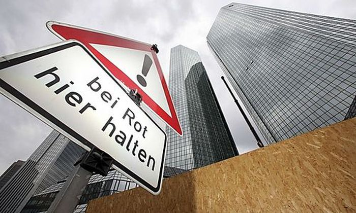 The headquarters of Deutsche Bank are pictured next to traffic sign that reads stop here on red ligh