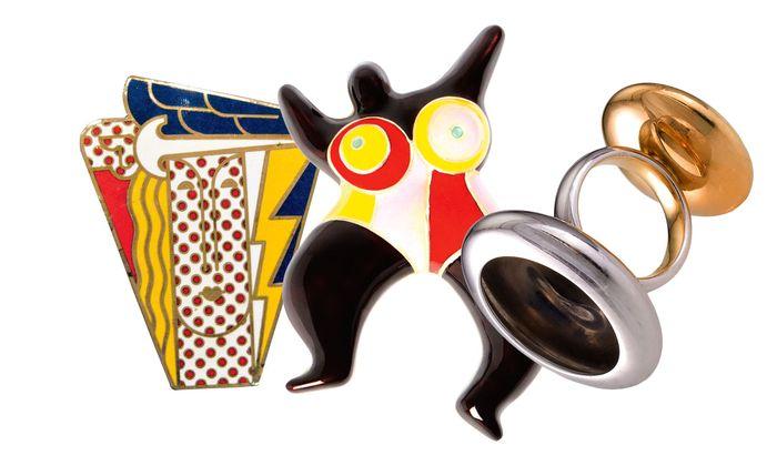 """V.l.n.r.: Roy Lichtenstein: Brosche """"Modern Head"""", 1968. Niki de Saint Phalle: Brosche """"Brown Nana"""", 1973. Anish Kapoor: """"Two-sided Ring"""" in Gelb- und Roségold, 2005."""